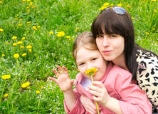 Mother and the daughter on a green meadow. With dandelions Royalty Free Stock Image