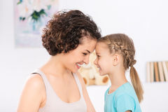 Mother and daughter are grinning to each other Royalty Free Stock Image