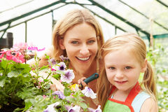Mother And Daughter Growing Plants In Greenhouse royalty free stock photo