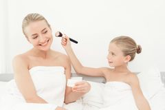Mother and daughter had a day of spa. They have fun in white bath towels. Daughter puts on the makeup of the mother with a makeup brush Stock Photography