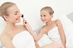 Mother and daughter had a day of spa. They have fun in white bath towels. Daughter puts on the makeup of the mother with a makeup brush Royalty Free Stock Photography