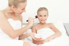 Mother and daughter had a day of spa. They have fun in white bath towels. Mother puts on the makeup to her doughter with a makeup brush Stock Photos