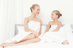 Mother and daughter had a day of spa. They have fun in white bath towels. They sit on the bed and look at each other Royalty Free Stock Images