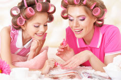 Mother and daughter in hair curlers. Portrait of happy Mother and little daughter in hair curlers with magazine at home stock photos