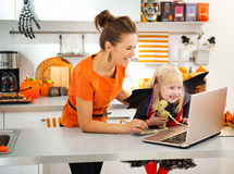 Mother with daughter in halloween bat costume having video chat Royalty Free Stock Photo