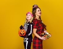 Mother and daughter with Halloween candies looking up. Colorful halloween. smiling modern mother and daughter in Mexican style halloween costume on yellow Royalty Free Stock Photography