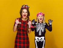 Mother and daughter in halloween costume frightening. Colorful halloween. smiling modern mother and daughter in Mexican style halloween costume isolated on stock photo