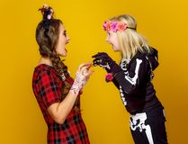 Mother and daughter in halloween costume frightening each other. Colorful halloween. modern mother and daughter in Mexican style halloween costume isolated on stock photography