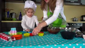 Mother and daughter hands preparing dough for cup-cake on table. stock video