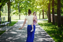Mother with the daughter on hands walk in park. rear view Stock Photo