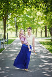 Mother with the daughter on hands walk in summer  park in sunny Stock Photo