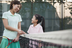 Mother and daughter handshaking over the tennis net Stock Images