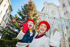 Mother and daughter handwaving near Christmas tree in Florence Stock Photography