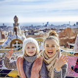 Mother and daughter handwaving while sitting on bench, Barcelona Royalty Free Stock Photos