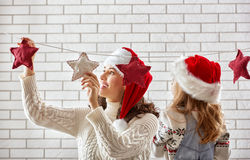 Mother and daughter hang a garland Royalty Free Stock Images
