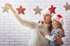 Mother and daughter hang a garland Stock Photo