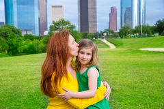 Mother and daughter happy hug kiss in park at city skyline Stock Images
