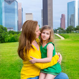 Mother and daughter happy hug in park at city skyline Royalty Free Stock Image