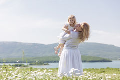 Mother with daughter. Happy mother playing with her daughter in flower field Royalty Free Stock Photos