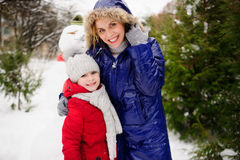 Mother with daughter have built a snowman and rejoice. Stock Photo