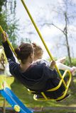 Mother and daughter have fun in the children`s park on a swing stock photography