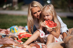 Mother with daughter have fun on the grass. Mother with daughter , the daughter eats melon stock photos