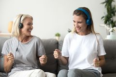 Mother and daughter have fun listening to music in headphones royalty free stock images