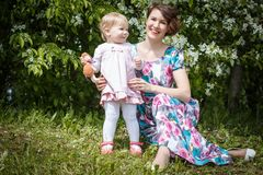 Mother and daughter have fun in the park and apple tree with white flowers Stock Photos