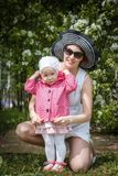 Mother and daughter have fun in the park and apple tree with white flowers Royalty Free Stock Photo