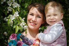 Mother and daughter have fun in the park and apple tree with white flowers Royalty Free Stock Image