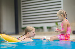 Mother and daughter have fun at pool side in tropical beach reso Stock Photography
