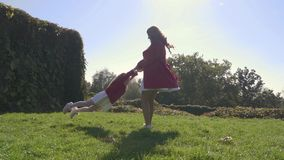 Mother spinning her daughter around in the park stock video