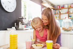 Mother And Daughter Having Breakfast At Kitchen Table Royalty Free Stock Photography