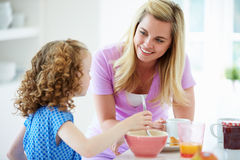 Mother And Daughter Having Breakfast In Kitchen Together Royalty Free Stock Images