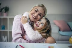 I love you mommy. Mother and daughter at home. Mother and daughter having education at home and hugging. Close up royalty free stock photography