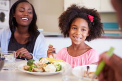 Mother And Daughter Having Family Meal At Table. Happy Mother And Daughter Having Family Meal At Table In Kitchen Royalty Free Stock Photo