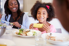 Mother And Daughter Having Family Meal At Table. Holding Corn On The Cob Smiling At Camera Royalty Free Stock Photography