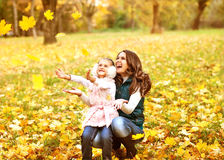 Mother and daughter having fun in the autumn park among the fall Royalty Free Stock Photo