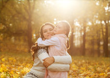 Mother and daughter having fun in the autumn park among the fall Royalty Free Stock Images