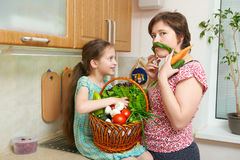Mother and daughter having fun with basket of vegetables and fresh fruits in kitchen interior. Parent and child. Healthy food conc Royalty Free Stock Image