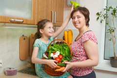 Mother and daughter having fun with basket of vegetables and fresh fruits in kitchen interior. Parent and child. Healthy food conc Royalty Free Stock Images