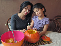 Mother and Daughter Having Fun While Carving a Halloween Pumpkin Royalty Free Stock Photo