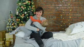 Mother and Daughter Having Fun on Christmas in Slow Mothion. Mother and Daughter Having Fun on the Bed near the Christmas Tree in Slow Motion stock video footage