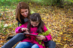Mother and daughter having fun on digital tablet in nature Stock Images