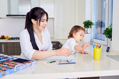 Mother and daughter are having fun while drawing at home. Royalty Free Stock Photography