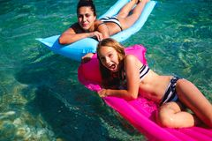 Mother and daughter having fun on floating beds stock photography