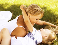 Mother with daughter having fun on grass Stock Photo