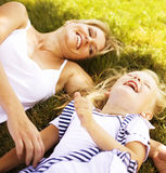 Mother with daughter having fun on grass Stock Photos