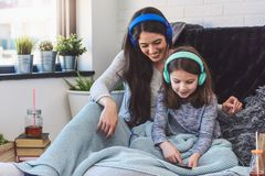 Mother and daughter having fun at home listening music Stock Photo