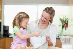 Mother and daughter having fun in the kitchen. Mother and daughter having fun together in the kitchen royalty free stock images